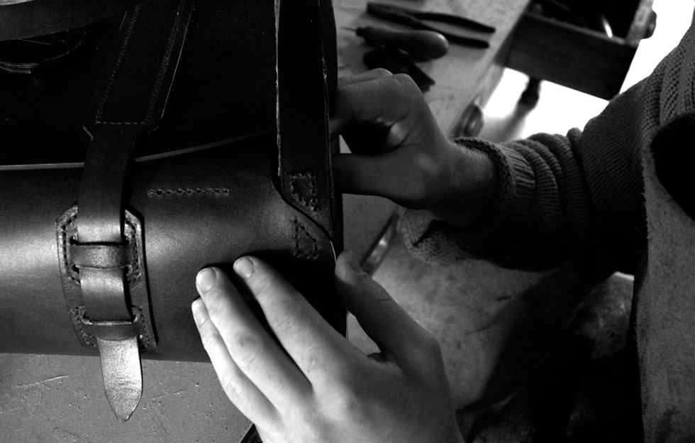 Hand stitching the shoulder strap detail on the 'Parachuter Bag'